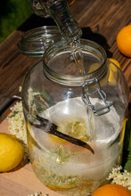 Pour The Vodka Into The Big Preserving Jar With The Fresh Elderflowers, Oranges And Lemon Slices, Sugar And The Vanilla Pod For The Elderflower Liqueur