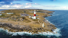 Aerial View Of Portland Bill Lighthouse With Waves Crashing On Rocks, Uk.