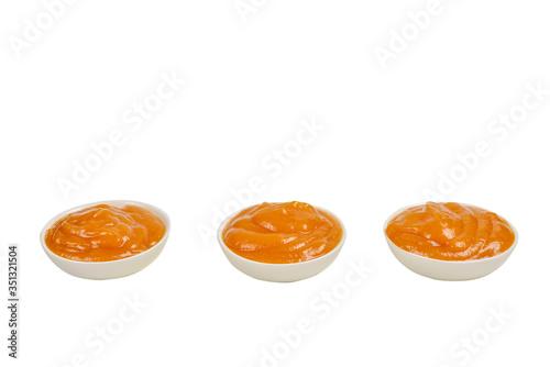 Orange sauce in white plate on white background.