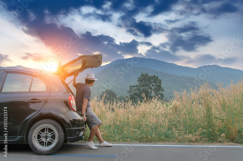 Fototapeta Man traveler sitting on hatchback black car with mountain view background in country road,Travel in holiday concept. obraz