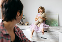Mother Working At Home, Daughter Sitting With Teddy Bear On Sideboard
