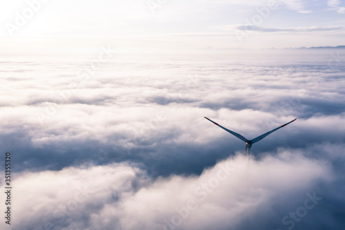 Germany, Aerial view of wind turbine shrouded in clouds at dawn - 351355320