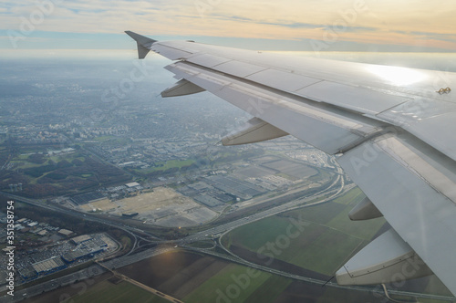 Obraz View over the clouds from the porthole of an airplane with plane wing over the Paris Airport area at take off - fototapety do salonu