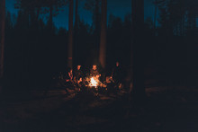 Friends Sitting At Campfire In The Woods