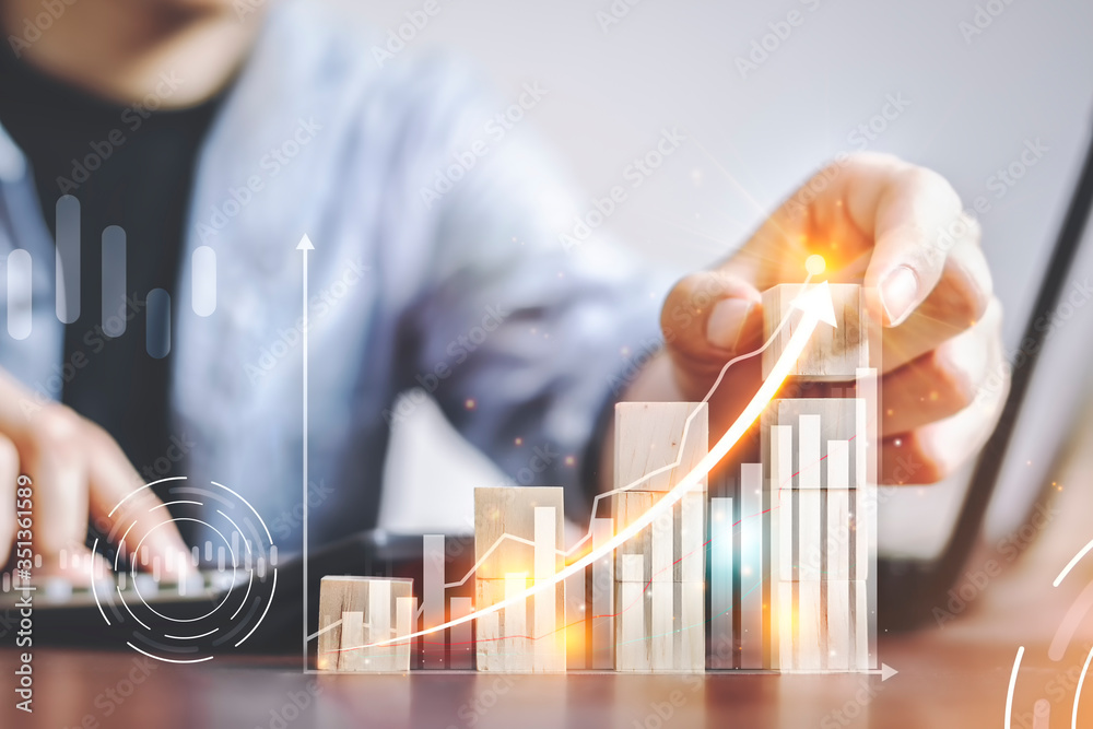 Fototapeta Businessmen use the finger to touch the wooden block that shows the business graph shown in the virtual screen. Plans to increase business and business growth Arrow the direction of growth and success