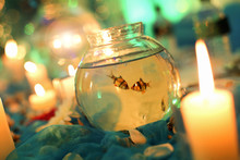 Fish In Bowl Amidst Burning Candles At Home
