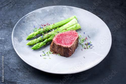 Obraz Gegrilltes dry aged Wagyu Filetkopf Medaillon Steak vom Rind natural mit grünen Spargel und Kräuter als closeup auf einem Modern Design Teller mit Textfreiraum - fototapety do salonu