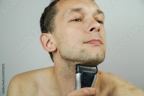 Fotografie, Tablou Portrait of a beautiful dark-haired man with an electric razor on a light background