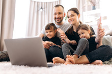 Good Time. Video Call. Family Leisure At Home. Happy Family Is Chatting With Grandparents By Video Conference On Laptop Sitting At Home On The Floor