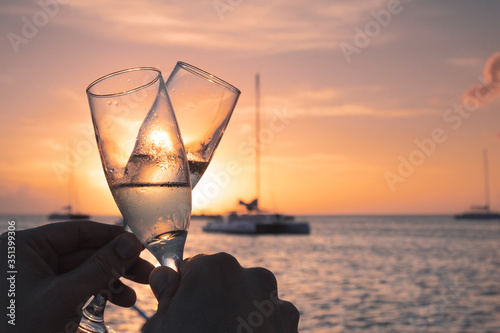 Close-up Of Hand Holding Champagne Glass Against Sunset Sky Fototapete