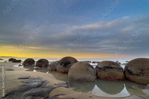 Fotografia Moeraki Boulders At Koekohe Beach Against Cloudy Sky During Sunset