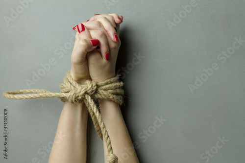 Fotografiet Close-up Of Hands Tied With Rope On Gray Background