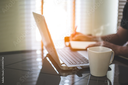 Close-up Of Hot Coffee In Cup By Laptop On Table Fototapet
