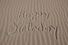 Happy Birthday Text Written On Sandy Beach
