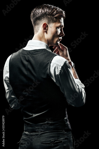Fotografija Rear View Of Young Man Standing Against Black Background