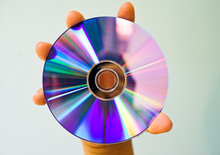 Close-up Of Hand Holding Compact Disc Against White Background