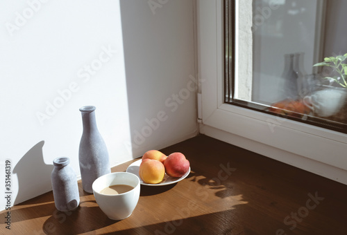 High Angle View Of Fruits With Drink On Wooden Table By Window