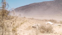 Wide Shot. Retro Campervan Drives On Desert Dirt Road Leaving Dust Trail.