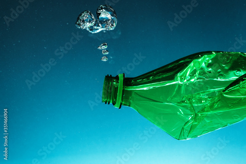 Obraz Crumpled plastic bottle polluting the ocean - fototapety do salonu