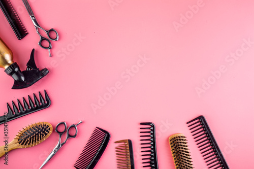 Fototapeta Combs, hairbrush, scissors - hairdresser eqiupment - on pink table top-down space for text obraz