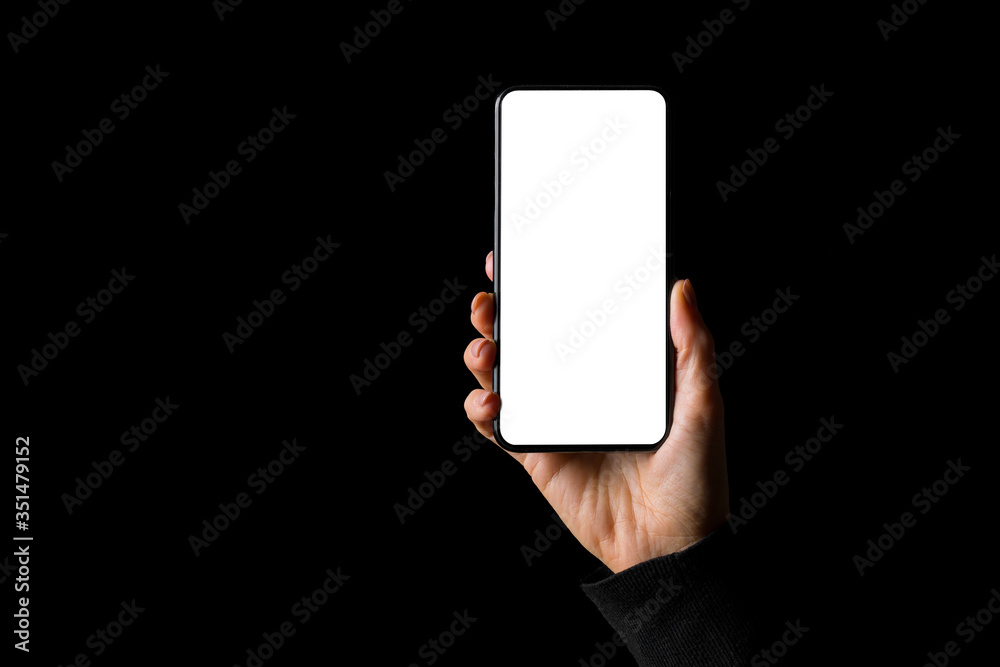 Obraz Person holding in hand smartphone with empty white screen, isolated on black background fototapeta, plakat