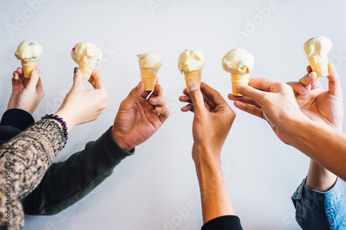 Fototapeta Cropped Hands Holding Ice Cream Cones Over White Background obraz na płótnie