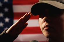 Memorial Day. A Female Soldier In Uniform Salutes Against The Background Of The American Flag. Close-up Portrait. The Concept Of The American National Holidays And Patriotism