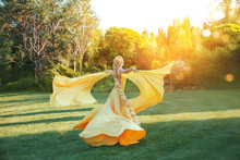 Bright Divine Sun Light. Art Fantasy Happy Woman Dancing Spinning Hand Raised Yellow Silk Dress, Cape Train Fluttering Fly In Wind. Blonde Girl Hairstyle Long Braid. Princess Rapunzel Back Rear View
