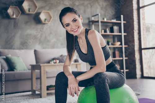 Obraz Photo of beautiful lady quarantine hobby training stay home record video blog dynamic practicing house fitness sitting on fit ball telling how to do exercise living room indoors - fototapety do salonu
