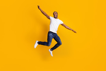 Full length body size view of his he nice attractive cheerful cherry guy jumping having fun weekend vacation free time isolated over bright vivid shine vibrant yellow color background