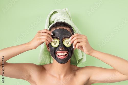 Obraz na plátně Happy smiling girl applying facial carbon mask portrait - Young woman having ski