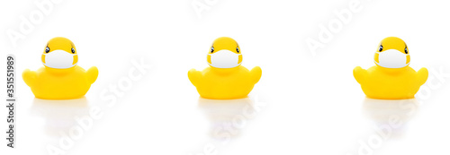 Fototapeta cute yellow rubber ducks in face masks on white background, concept of social di