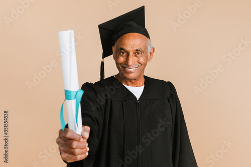Proud senior man in a graduation gown holding his diploma Fototapet