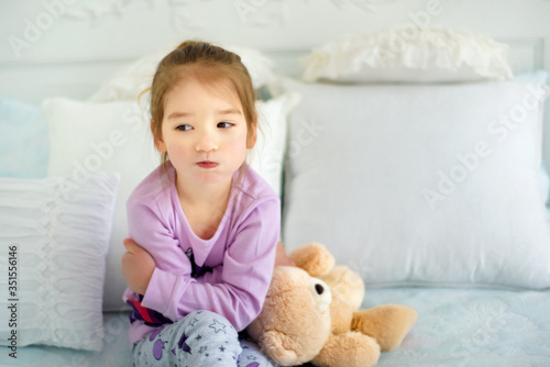 Portrait of small 3 years old sulking capricious girl sitting in bed in pajama with her toy bear Fototapeta