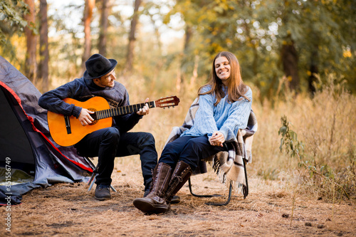Fotografía Portrait of young couple sitting on camp chair with guitar near camp tent