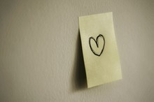 Close-up Of Adhesive Note With Heart Shape Stuck On Wall