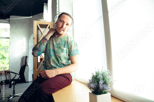 Young caucasian man gesturing during a video conference, sitting in armchair in the living room. Communication during insulation, pandemic, remote working or meeting with friends, family.
