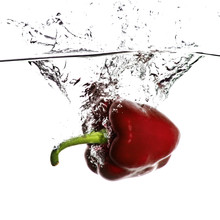 Close-up Of Red Bell Pepper Splashing Water On White Background