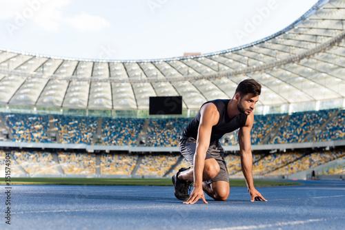 Obraz handsome runner in start position on running track at stadium - fototapety do salonu