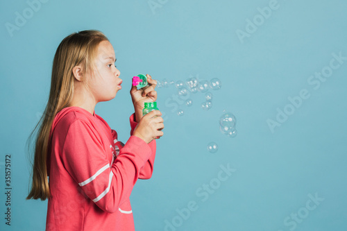 Cute girl with Down Syndrome blowing bubbles Canvas Print