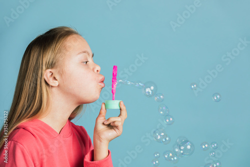 Fototapeta Cute girl with Down Syndrome blowing bubbles