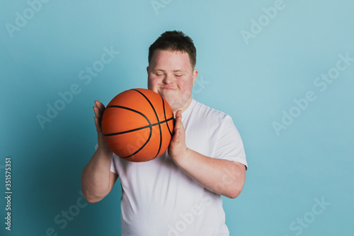 Fotomural Cute athletic boy with down syndrome holding a basketball