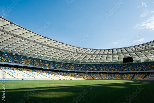 Obraz grassy football pitch at stadium at sunny day with blue sky - fototapety do salonu