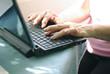 Manos que escriben en el teclado de un ordenador portatil