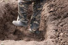 Man Digs A Deep Pit. Digging A Pit By Shovel.