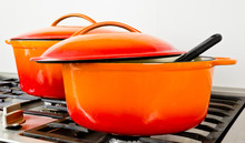 Two Bright Orange Pots From Cast Iron With Enamel At An Old Vintage Gas Stove