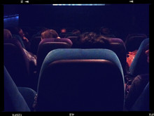 Rear View Of People Watching Movie In Theatre