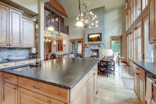 Fotografía Large luxury wooden kitchen interior with light wood hardwood floor and dark granite slab on island with huge windows