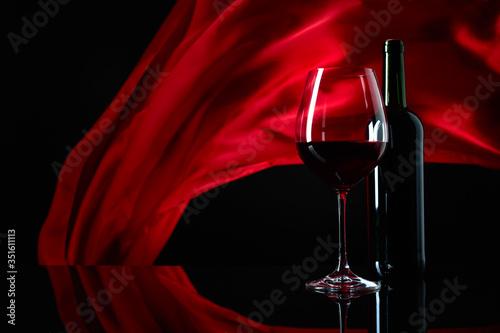 Obraz na plátně Wineglass and bottle of red wine on a black reflective background