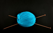 Ball Of Wool With Knitting Needles Against Black Background